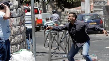 Un policier israélien en tenue civile pointe son arme vers un Palestinien, tandis que ses collègues arrêtent des manifestants, au cours de heurts ayant éclaté après la traditionnelle prière du vendredi. Jérusalem, le 25 juillet.