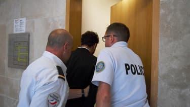 Le chanteur marocain Saad Lamjarred escorté par des officiers de police au tribunal d'Aix-en-Provence, le 18 septembre 2018