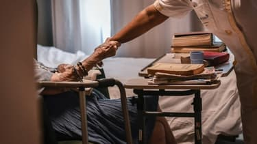 Image d'illustration - Une personne âgée tenant le bras d'une aide-soignante dans un établissement EHPAD parisien - STEPHANE DE SAKUTIN / AFP