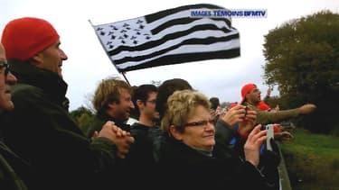 Des manifestants en Bretagne regardent un portique écotaxe partir en flammes.