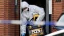 Un enquêteur sort du domicile du suspect dans le quartier de Molenbeek.