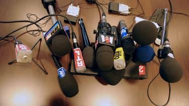 Des micros de différents médias sont posés sur une table, le 25 février 2011
