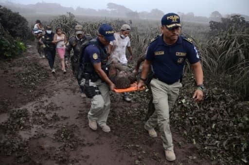 Des policiers évacuent un blessé lors de l'érruption du volcan Fuego, dans le village d'El Rodeo village, à 35 km au sud de la ville Guatemala le 3 juin 2018