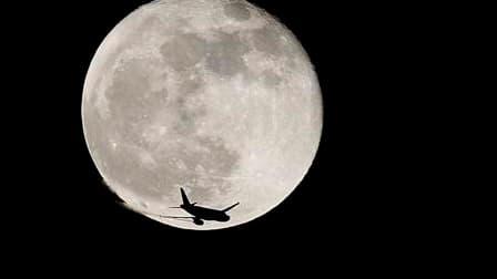 Un avion devant la lune - Image d'illustration