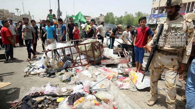 Un membre des forces de sécurité irakiennes monte la garde, alors que les civils regardent les dégâts causés par l'attaque de Daesh, dans un marché de Bagdad, le 11 mai 2016.