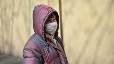 Une femme avec un masque protecteur devant l'hôpital de Huashan à Shanghai, le 21 janvier 2020 en Chine