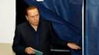 Silvio Berlusconi dans un bureau de vote à Milan. Les scandales de corruption et les bévues administratives du parti du président du Conseil ont porté un coup à la participation dimanche aux élections régionales italiennes, ce qui pourrait favoriser l'opp