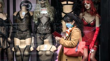 Une passante portant un masque devant un sexshop fermé dans le quartier de Pigalle, à Paris, le 16 mars 2020
