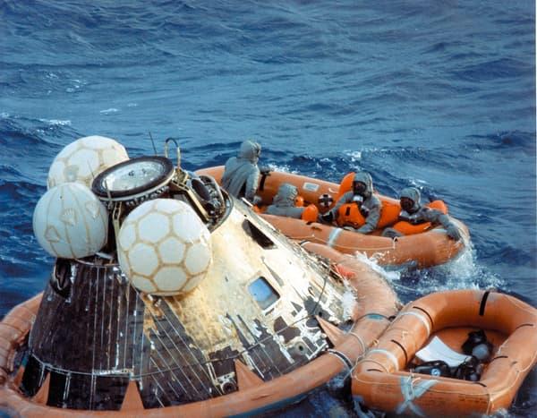 Neil Armstrong, Buzz Aldrin et Michael Collins peu après leur amerrissage dans l'océan Pacifique, accompagnés d'un militaire chargé de les décontaminer.