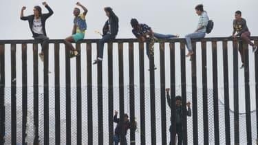 Des migrants qui ont participé à la caravane des migrants escaladent la barrière entre la frontière mexicaine et les Etats-Unis, le 29 avril 2018 à San Ysidro, en Californie