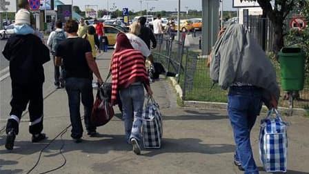 """Arrivée à Bucarest d'une famille de Roms reconduite en Roumanie depuis la France cet été. Le Parlement européen a demandé à Strasbourg aux Etats européens, dont la France, seul pays à être cité, de """"suspendre immédiatement toutes les expulsions de Roms""""."""