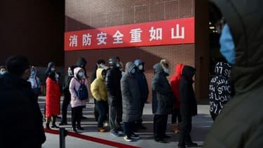 Personnes patientent pour réaliser un test du Covid-19 à l'extérieur d'un hôpital de Pékin, le 5 janvier 2021