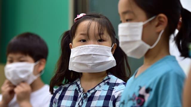 Des enfants portent des masques de protection lors d'un cours de prévention contre le coronavirus MERS, le 2 juin, à Séoul, en Corée du Sud.