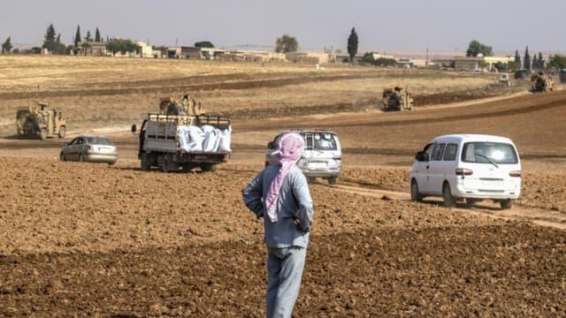 Un homme regarde les patrouilles de véhicules militaires turques, au nord-est de la Syrie dans la province d'Hasakek, le 1er novembre 2019