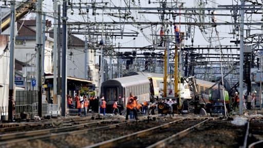 Une grue a permis le levage d'une première voiture du train qui a déraillé, ce vendredi, à Brétigny-sur-Orge le 13 juillet 2013.