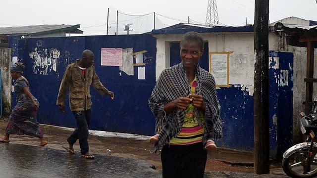 Des Libériens marchent devant l'ancienne école, transformée en centre d'isolement, d'où 17 malades se sont échappés.