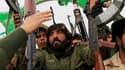 Soldats libyens à Ajdabiah, dans l'Est du pays. Le ministère de la Défense à Tripoli a prévenu jeudi que toute intervention étrangère mettrait en danger le trafic aérien et maritime en Méditerranée. /Photo prise le 16 mars 2011/REUTERS/Ahmed Jadallah
