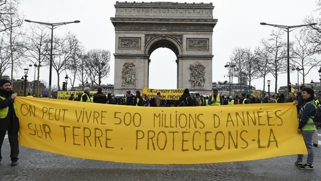 """Des gilets jaunes défilent avec une banderole """"On peut vivre 500 millions d'années sur Terre. Protégeons-la"""", le 9 mars 2019 à Paris."""