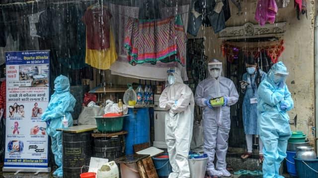 Des soignants en combinaison de protection s'abritent de la pluie à Bombay (Inde) le 12 août 2020.