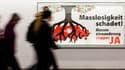 """Des passants à Zurich devant une affiche contre """"l'immigration de masse"""" en Suisse."""