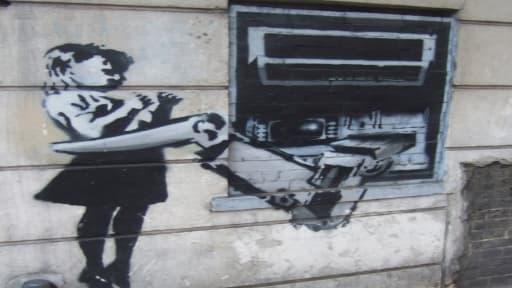 Un tag du graffeur britannique Banksy près d'un distributeur de billets