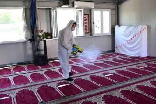 Un homme désinfecte des tapis après la prière du vendredi dans une mosquée de Milan, le 5 juin 2020