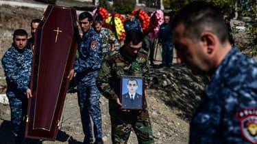 Un homme porte le portrait d'un soldat mort au combat dans la région séparatiste du Haut-Karabakh, le 17 octobre 2020.