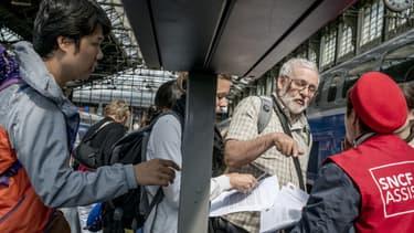 """Gare de Lyon, les passagers cherchent à s'orienter auprès des """"gilets rouge"""" de la SNCF."""