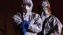 Responsables japonais en tenue anti-contamination non loin de la centrale de Fukushima.