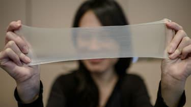 Une femme tire sur l'un des échantillons du plus mince préservatif en latex du monde lors d'une conférence de presse à Hong Kong, le 20 février 2014. Les préservatifs fabriqués par la société chinoise Guangzhou Daming United Rubber Products.