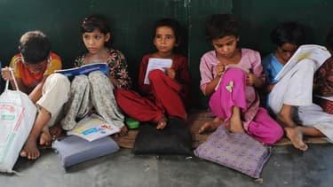 Des élèves lisent dans une salle de classe, dans l'Uttar Pradesh, en Inde, le 30 août 2012.
