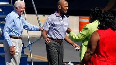 Aijalon Mahli Gomes (au centre), un Américain emprisonné pour avoir pénétré en territoire nord-coréen, retrouve ses proches à l'aéroport de Boston sous les yeux de l'ancien président Jimmy Carter (à gauche), qui a obtenu sa libération. Cet enseignant avai