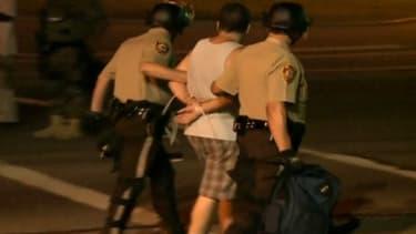 Interpellation d'un manifestant par la police, dans la nuit de lundi à mardi à Ferguson, dans le Missouri.