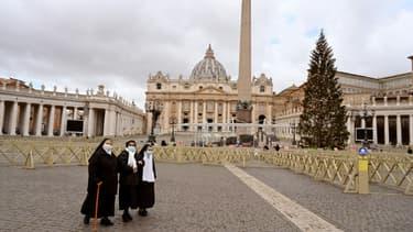 Des religieuses marchent sur la place Saint-Pierre déserte à cause du confinement lié à la pandémie de coronavirus, à Rome le 25 décembre 2020