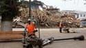 Employés municipaux à l'oeuvre à Constitucion. Le gouvernement chilien a ramené le bilan du séisme de samedi à 279 morts après avoir fait état de 802 décès. /Photo prise le 4 mars 2010/REUTERS/Enrique Marcarian