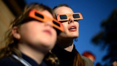 Personnes regardant une éclipse après avoir chaussé des lunettes de protection spéciales. (Illustration)