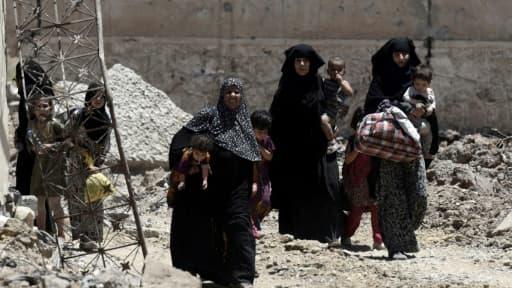 Des femmes irakiennes fuient leur foyer le 15 juin 2017 dans le quartier al-Shifa à l'ouest de Mossoul