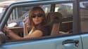 Femme fumant dans un voiture, alors qu'un enfant est assis à l'arrière.