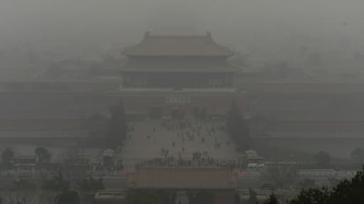 Des visiteurs dans la Cité Interdite marchent sous un nuage de pollution, à Pékin, le 26 février 2014. C'est en Asie du Sud-Est, qu'il y a le plus de décès provoqués par l'environnement, avec un total de 3,8 millions, selon l'OMS