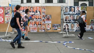 Des passants devant des affiches électorales pour les scrutins du 26 mai 2019 en Belgique (photo prise le 18 mai 2019 à Bruxelles)