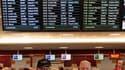 Devant le tableau des départs à l'aéroport d'Edimbourg, en Ecosse. La propagation du nuage de cendres volcaniques a conduit mardi à l'annulation de dizaines de vols en Ecosse et à la fermeture partielle de l'espace aérien danois mais les experts estiment