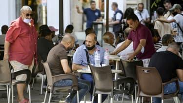 Des personnes sont assises à une terrasse de café le long de l'avenue Habib Bourguiba à Tunis,  le 28 juillet 2021