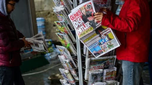 """Un homme regarde le journal turc Günes qui publie à sa """"Une"""" un photomontage de la Chancelière allemande Angela Merkel dépeinte en Hitler, le 17 mars 2017 à Istanbul"""