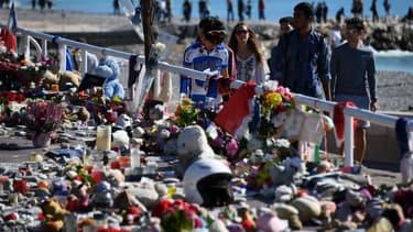 Des passants regardent des fleurs et bougies déposées en mémoire des victimes de l'attentat du 14 juillet 2016 à Nice, le 15 octobre suivant. (Photo d'illustration)
