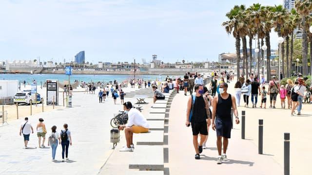 Légende AFP: Les gens marchent sur la promenade de la plage de Bogatell le 6 juin 2021 à Barcelone. L'Espagne autorisera tous les voyageurs vaccinés à visiter le pays à partir du 7 juin, car le point chaud du tourisme vise à relancer son industrie du voyage battue par les virus.