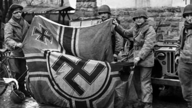 Des soldats anglais tenant un drapeau nazi au moment de la libération