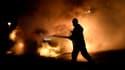 Un pompier éteint une voiture incendiée lors des émeutes qui secouent la capitale suédoise.