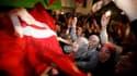 Des partisans de la formation islamiste Ennahda célèbrent leur victoire aux élections constituantes de mardi, devant le siège du parti à Tunis. Ennahda a dit mardi soir avoir gagné plus de 40% des sièges. /Photo prise le 25 octobre 2011/REUTERS/Zohra Bens