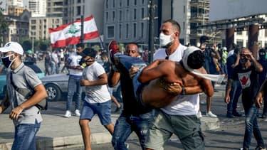 La star du basketball au Liban Fadi al-Khatib transporte en courtant un manifestant blessé lors des manifestations à Beyrouth contre le pouvoir, le 8 août 2020
