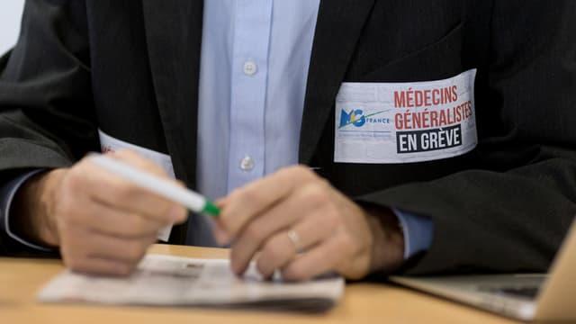 """Un médecin portant un sticker """"Médecins généralistes en grève"""", le 23 décembre 2014 à Paris."""